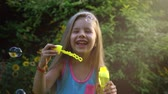 soap bubbles : Happy child blowing soap bubbles in park. Slow motion. Stock footage.