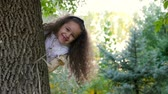 vesta : Beautiful Fashionable Happy Smiling Stylish Joyful European Little Cute Girl in a White Vest and Long Blond Curly Hair Walks through the Autumn Park, Looks out From Behind the Tree and Looks into the Camera. . Autumn Concept