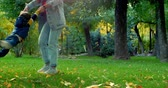 colete : Beautiful Happy Smiling Stylish Joyful European Cute Mother in a Denim Suit and Long Curly Hair Walks Through the Autumn Park with a Beautiful Little Son of Two Years, Mom and Baby Dancing. Family Concept Vídeos