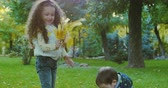 présenter : Beautiful Fashion Happy Smiles Stylish Joyful European Little Cute Brother and Sister Have Fun Walking in Autumn Park, Happy to Play with Autumn Foliage, Boy Dends a Bouquet of Leaves to His Beloved Sister, Girl Kisses His Little Brother. Concept de famille. Vidéos Libres De Droits