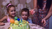 explodindo : Concept of a happy family. Happy little boy of two years celebrates his birthday with his family, his mother and little sister helped him blow out the candles.