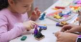 ismeretlen : Cute Little Children Sitting at the Desk Sculpts a Different Figures From Made of Colored Modeling Plasticine in the Nursery. Development of the Art of Modeling in Children. Stock mozgókép