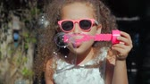 batole : Happy Little Girl playing outdoor, blowing soap bubbles, having fun on backyard. Nature. Beautiful Child in Park.