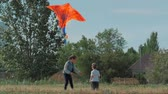 Rear View Children Play With a Kite, a Little Girl and a Boy Let a Flying Snake in the Meadow. Happy and Carefree Childhood.