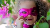 pelerin : Beautiful Llittle Girl in the Superhero Costume, Dressed in a Pink Cloak and the Mask of the Hero. Plays on the Background of the Sea and the Blue Sky and Clouds, Corrects the Pink Mask on His Face