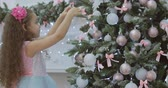 zdobení : CU little girl with curly hair in a festive dress, hanging Christmas decorations on the Christmas tree with Christmas lights. Decoration on the Christmas tree with a ball. 4K