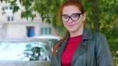 on : Portrait of an attractive smiling young woman with glasses close-up face of a happy woman with long red hair in a good mood, positive emotions.