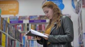 prateleira de livros : Portrait of a Young Beautiful Woman with Bright Red Hair in Glasses, Pretty Girl Reading in Book Library University. Vídeos