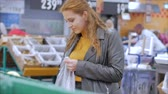 laranjas : Pretty young beautiful red hair woman buys food, fruits, apples in the market, in the supermarket.Girl chooses products,vegetables, fruits in the store.Shopping,Vegan sales concept. Vídeos