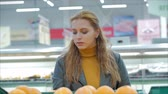 naranjas : Pretty young beautiful red hair woman buys food, fruits, apples, oranges in the market, in the supermarket.Girl chooses products,vegetables, fruits in the store.Shopping,Vegan sales concept.