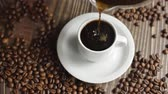 krem : Coffee cup and coffee beans. White cup of evaporating coffee on the table with roasted bean. Slow Motion coffee pour. Wideo