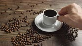 krem : Male Hand takes a mug of coffee.Coffee cup and coffee beans. White cup of steaming coffee on the table with roasted bean.