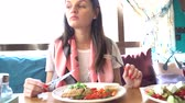 рестораны : Close up of salad, which is being eaten by young lady in restaurant.
