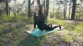 těhotná : young pregnant woman doing yoga outside.