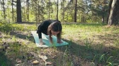 Вы : young pregnant woman doing yoga outside.