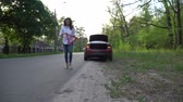 warsztat samochodowy : Woman is placing a warning triangle and calling roadside assistance.