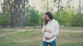 expectante : pregnant woman holding her belly walking under summer tries
