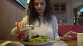 ebéd : Woman eating salad in an indoor cafe, close up on a plate.