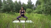 mladí dospělí : young pregnant woman doing yoga outside.