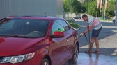 lavagem : Young caucasian man washing his car on the car wash self-service. Car washing.