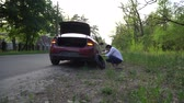 Pregnant woman changing a punctured tire at the car. repair of cars on the road. Stok Video