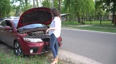 Pregnant woman and broken car calling for help on cell phone. Stok Video