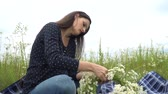 Pregnant woman making camomile wreath. Stok Video