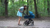 kinderen lopen : Mother walking with a pram in the park. Summer nature background. Stedycam.