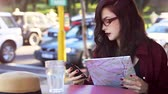 Pretty young traveller girl looking at map and cell phone at outdoors cafe Stok Video