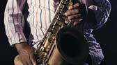 African man colored old black playing saxophone dark background music hands Stok Video