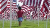 американский флаг : Boy walking amongst American flags and saluting