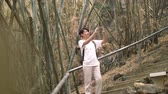 칸차나 부리 : a tourist guy use mobile phone chatting in bamboo jungle forrest