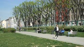 article : People enjoy spring on a bench in a pedestrian path in the Porta Ticinese district in Milan, Italy