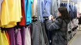 cardigã : A young girl chooses a leather jacket in shop, sorting out things on a hanger