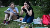 course pied : MOSCOW, RUSSIA - 21 JULY 2018: Man and young woman in the sunny summer park. relax and eat burgers with sausages. Rendezvous and picnic in the summer park on grass.