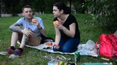 woman s day : MOSCOW, RUSSIA - 21 JULY 2018: Man and young woman in the sunny summer park. relax and eat burgers with sausages. Rendezvous and picnic in the summer park on grass.