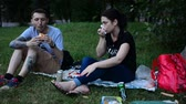heteroszexuális párok : MOSCOW, RUSSIA - 21 JULY 2018: Young People Eating Sandwiches and Drinking Beer, Have Picnic on a Lawn and Talking, Smiling. Sitting on a Green Grass in Park. Happy Teenagers Have Some Food.