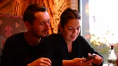 karczma : Young couple in cafe browsing internet on smart phone