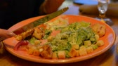 císař : Macro closeup of caesar salad on plate with red tongs, parmesan cheese, dressing, tongs, people moving, eating in background Dostupné videozáznamy