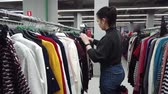 decidir : Young women shopping in fashion mall, choosing new clothes, looking through hangers with different casual colorful garments on hangers