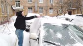 balai : Young Woman Cleaning Car from Snow and Ice Vidéos Libres De Droits