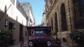 HAVANA, CUBA - APRIL 2019: Havana is an iconic popular tourist destination. Old streets of Havana. Classic American Vintage Retro Cuban Cars driving on the street of Havana city, Cuba. Wideo
