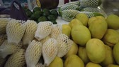 ananász : Sale tropical Vietnam fruits on the counter of the market. Girl chooses exotic fruits in the store. Stock mozgókép