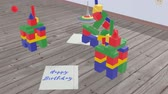 colapso : Kids spinning top runs between the cubes and a sheet of blue lettering - Happy Birthday