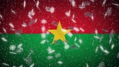 Burkina Faso flag falling snow loopable, New Year and Christmas background, loop. Stok Video