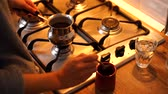 fornuis : Woman make coffee in cezve in modern kitchen at home