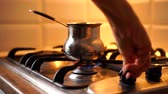 fornuis : Woman turn on the gas stove to prepare coffee in cezve at home