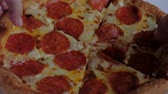 sausage slice : two people take a slice of pepperoni pizza out of the box. junk food