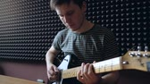 Musician plays on electro guitar in the Studio. Slowmotion.