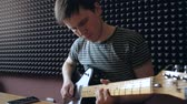 Musician plays on electro guitar in the Studio using a smartphone. Slowmotion.